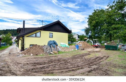 Rebuilding a family house and adding an extension. Setting up a construction site with tools excavator and construction material.