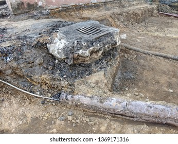 Rebuilding of street, broken manhole with steel cover. Manhole with rusty metal cover in cracked asphalt surface