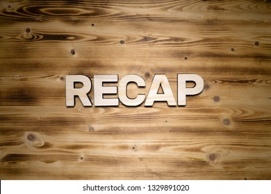 RECAP word made of wooden letters on wooden board.