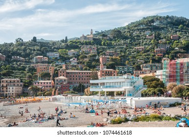 RECCO, ITALY - MAY 12, 2013: People rest and sunbathe on beach on Mediterranean coast