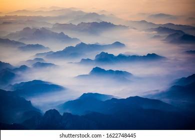 Receding Alps mountains in Austria, morning fog in the valleys