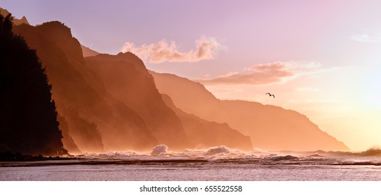 Receding headlands of the Na Pali Kauai coastline illuminated at sunset over a stormy sea with a distant bird. The mountains off Ke'e beach are the start of the Kalalau Trail