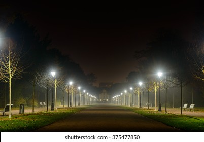 Receding perspective of an illuminated deserted street lit by two rows of street lamps at night disappearing into the distance with copy space above