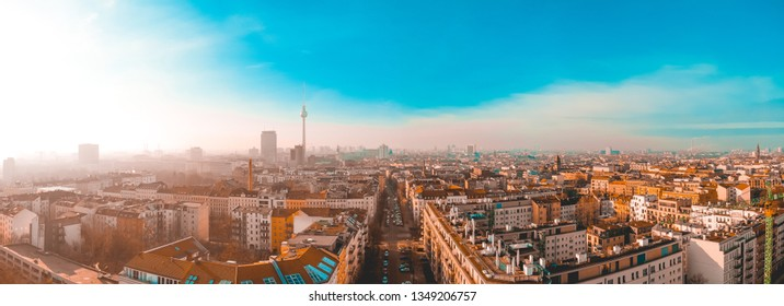 Receding perspective of a wide street in a historic city in a very wide angle panorama aerial rooftop view under a blue cloudy sky shot from a drone