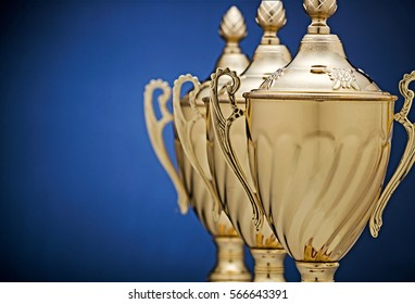 Receding staggered row of three gold trophy cups on a blue background with vignette and copy space conceptual of success, winning, challenge and competition