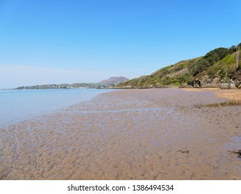 The receding waters of the River Dwyryd estuary leaves behind wet rippled sand in a small bay.