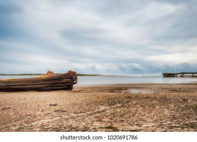 A receeding storm leaves behind calm waters and deserted beach, littered with large pieces of driftwood and trees, in the early evening hours at Siletz Bay in Lincoln City Oregon