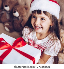 Receive a present.Christmas kids,child, portrait.Little girl in Santa Claus hat at home with Xmas tree.Close up,selective focus.