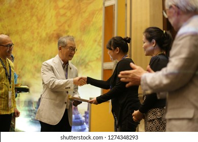 receiving a certificate give to asian woman on stage. certificate in hand. yogyakarta indonesia. january 04, 2019.