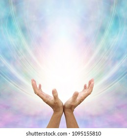 Receiving Divine Source of Healing - hands cupped and facing up towards white light and blue pink energy formation background with copy space