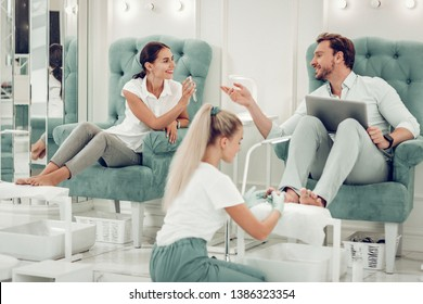 Receiving feet massage. Cheerful good-looking couple actively talking while sitting in armchairs in professional beauty salon