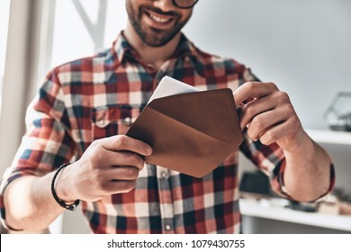 Receiving greeting card. Close up of young man opening envelope and smiling while standing indoors - Shutterstock ID 1079430755