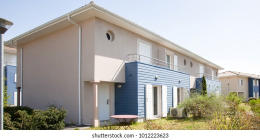 a recent building with a blue wooden siding of small semi-detached houses