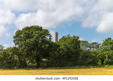 Recently harvested farmland with industrial paper mill chimney in the background.
