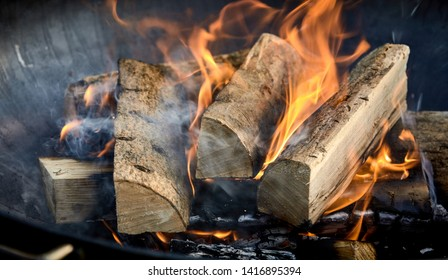 Recently lit fire with logs of flaming wood on a bed of chopped kindling in a portable summer barbecue in a close up panorama banner view