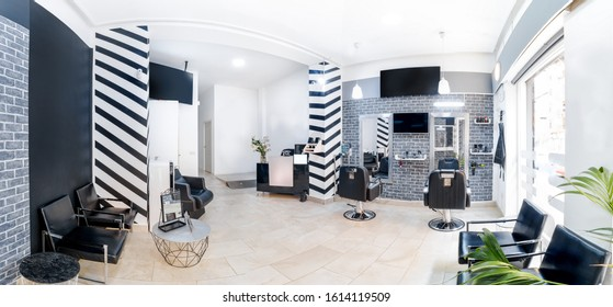 Reception in a beauty salon with desk,plant and banners. Panorama of a hair salon modern bright beauty salon interiorBlack and white decoration with mirrors, chairs,tv screen and mockup banners.