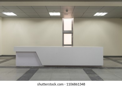 Reception desk in a corridor with large panoramic window with wide shades and rectangular pattern.
