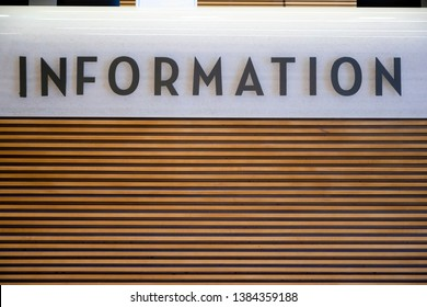 The reception desk is made of natural wooden slats, covered with colorless varnish, and packed horizontally on a frame covered with white granite stone with the sign Information