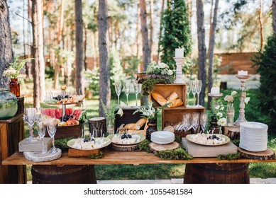 Reception table with snacks and lemonade decorated with candles on stands and  olawn on background. Food, decor. Wedding