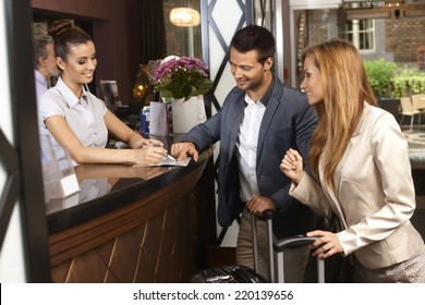 Receptionist giving tourist information to hotel guests upon arrival.