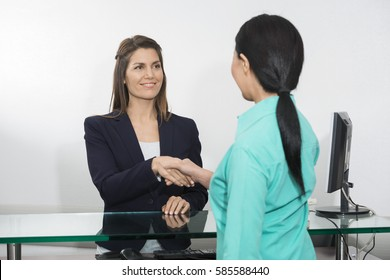Receptionist Shaking Hand With Patient In Hospital