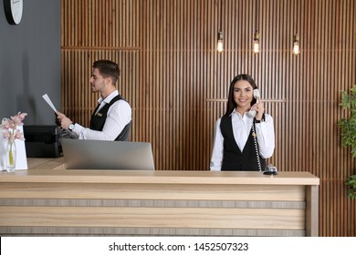 Receptionists working at desk in modern lobby