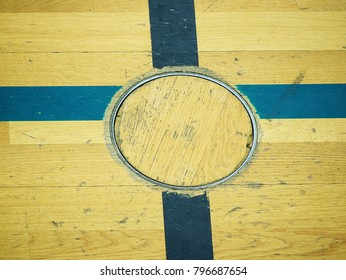 Recessed floor lid  for training equipment, Detail in floor of school gym. Black painted cross on wooden floor of sporting hall with sratched surface.