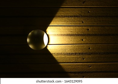 Recessed lighting in a wooden floor. The light from the lamp is beautifully and evenly, in a semicircle, extends to wooden boards. Part of the street lighting. Horizontal view. Top view. Copy space.