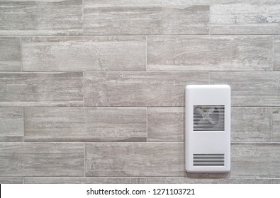 Recessed wall mounted heater against a grey ceramic wall