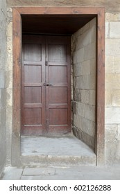 Recessed wooden aged engraved door and stone wall, Medieval Cairo, Egypt