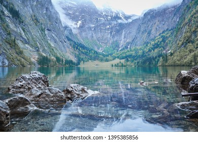 recflecting lake konigsee with view at distant waterfall rothbachfall