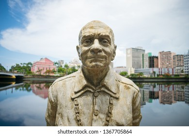 Recife, Brazil - Circa April 2019: Close up of the statue of author Ariano Suassuna by the river Capibaribe - historic center in the background
