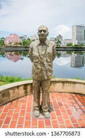 Recife, Brazil - Circa April 2019: Statue of author Ariano Suassuna by the river Capibaribe - historic center in the background