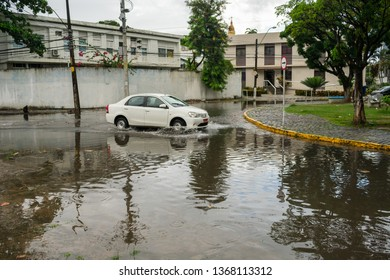 Recife, Brazil - Circa April 2019: Car passing on a street flooded after a few minutes of heavy rain. A frequent problem in Recife, Brazil