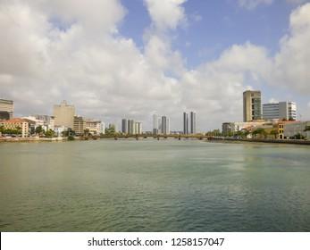 Recife, Brazil - Circa December 2018: A view of Capibaribe river with Mauricio de Nassau bridge and cityscape in the background