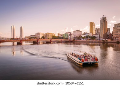 RECIFE, BRAZIL - MARCH 20: The architecture of Recife in Pernambuco, Brazil at sunset with its mix of contemporary and historic buildings by the Capibaribe river with tourists enjoying a boat tour.