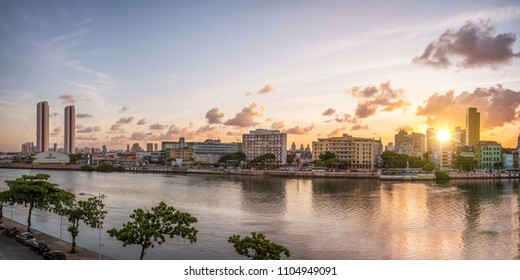 RECIFE, BRAZIL - MARCH 21, 2018: The historic architecture of Recife in the state of Pernambuco, Brazil with its colonial buildings mixed with contemporary ones at sunset by the Capibaribe River.