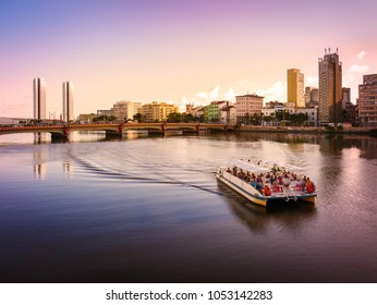 RECIFE, BRAZIL - MARCH 23, 2018: The architecture of Recife in PE, Brazil by the Capibaribe river showcasing its mix of contemporary and historic buildings at sunset with a tour boat passing by.