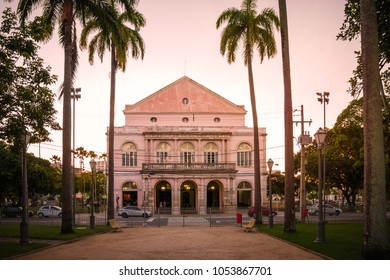 RECIFE, BRAZIL - MARCH 23, 2018: The historic architecture of Recife in Pernambuco, Brazil showcasing the Santa Isabel Theater at sunset among the imperial palm trees.