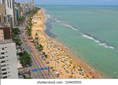 Recife, Pernambuco, Brazil, 2009. A view to the city beach with lots of Brazilian people sunbathing and swimming, and umbrellas, a view from the top of a skyscraper.