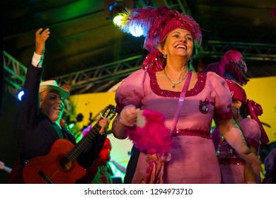 Recife, Pernambuco, Brazil, in February 2017. Carnival. Frevo: manifestation of the popular culture of Pernambuco.In the foreground, woman with pink dress. Behind, out of focus, a man with a guitar.