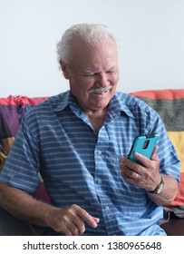 RECIFE, PERNAMBUCO, BRAZIL - MARCH 15, 2018:An old man enjoying his brand new cellphone