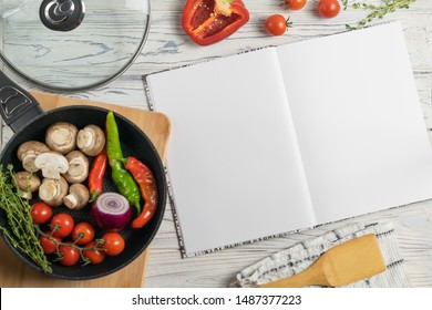 Recipe book with copy space for text, overhead composition with fresh organic ingredients in frying pan on wooden table