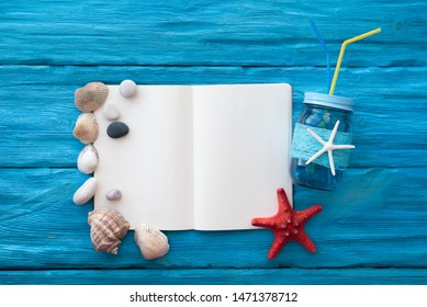 Recipe book mockup of sea cocktail over blue wooden background.