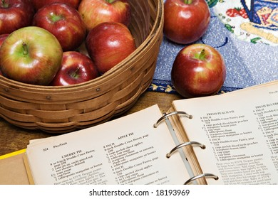 A recipe book turned to apple pie recipe - basket of apples.
