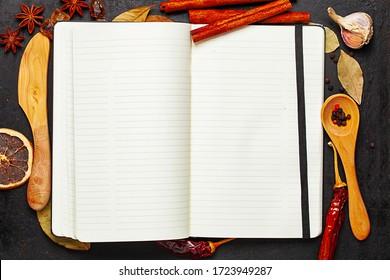 Libro de recetas, cuchillo de madera, cuchara y especies sobre el pasado rústico