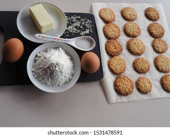 Recipe delicious sesame cookies in detail. Flour, eggs, sesame seeds, butter in plates, a spoonful of sugar on a dark stand and sesame cookies on parchment.
