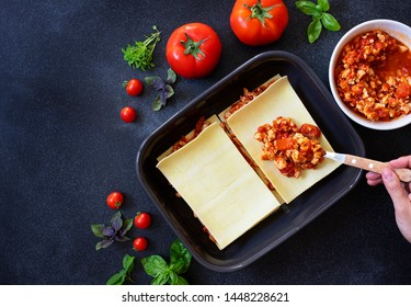 Recipe for homemade Italian lasagna with tomato sauce and meat. Phased recipe. Cooking lasagna. Spread meat sauce. Two portions. Dark background. Top view. Copy space