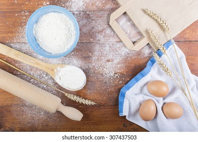 Recipe ingredients and kitchen utensils for cooking on wooden background, top view