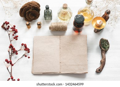 Recipe magic book and various dry herbs on a table of witch doctor or a herbal medicine essential oil on a table.